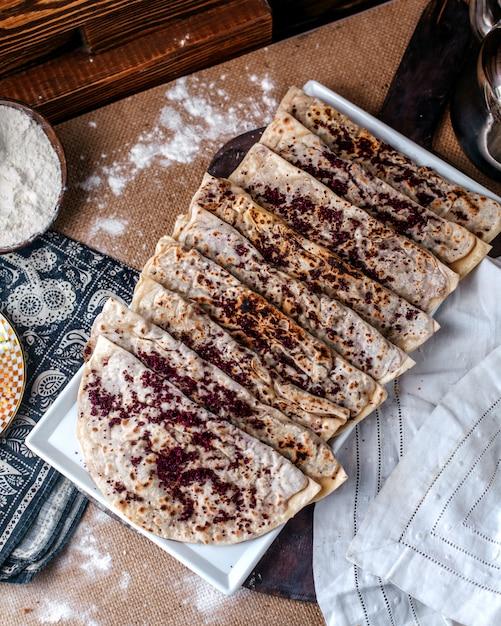 Vista superior qutabs famosa refeição de carne oriental com carne picada dentro e com tempero marrom chamado sumax dentro de chapa branca na superfície marrom Foto gratuita