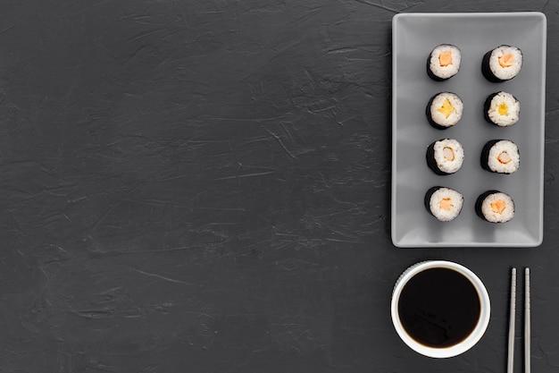 Vista superior rolos de sushi com molho de soja Foto gratuita