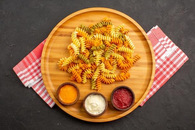 Vista superior saborosa massa italiana incomum massa espiral cozida com temperos no escuro Foto gratuita