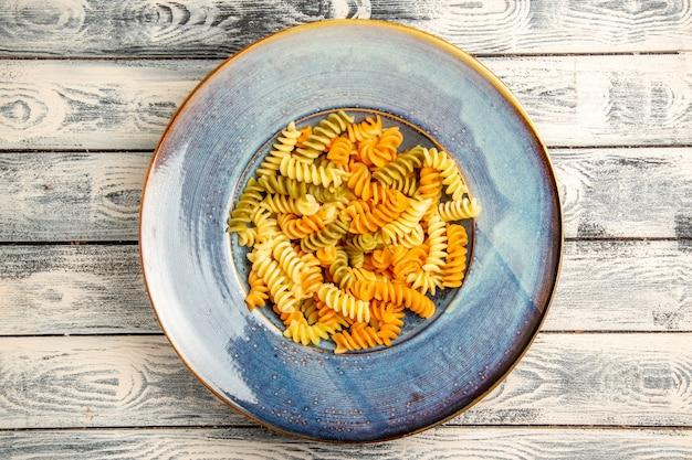 Vista superior saborosa massa italiana incomum massa espiral cozida em madeira cinza Foto gratuita