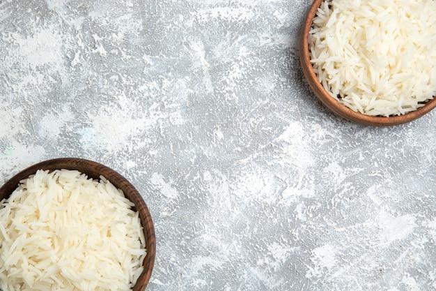 Vista superior saboroso arroz cozido dentro de pratos marrons no branco Foto gratuita