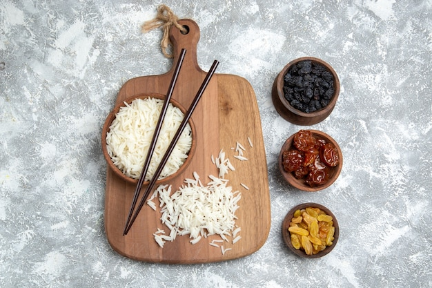 Vista superior saboroso arroz cozido dentro de um prato marrom com passas no branco Foto gratuita