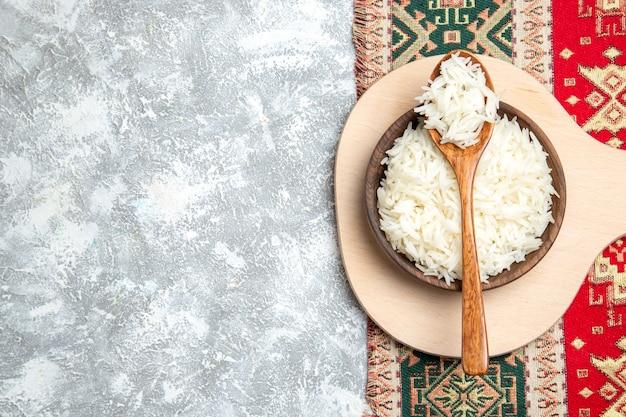 Vista superior saboroso arroz cozido dentro de um prato marrom em branco claro Foto gratuita
