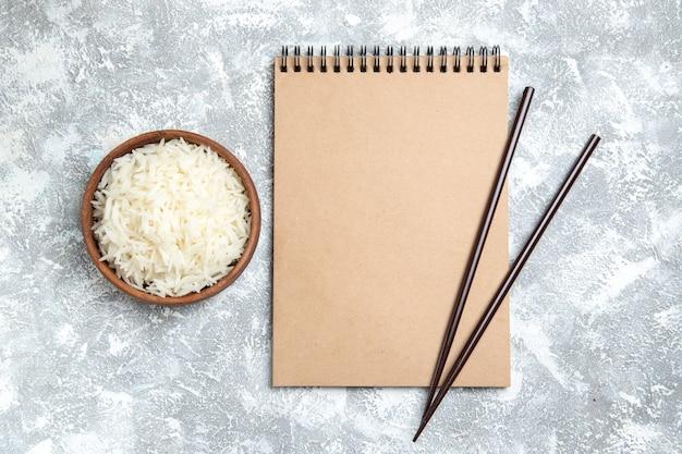 Vista superior saboroso arroz cozido dentro de um prato marrom no branco Foto gratuita