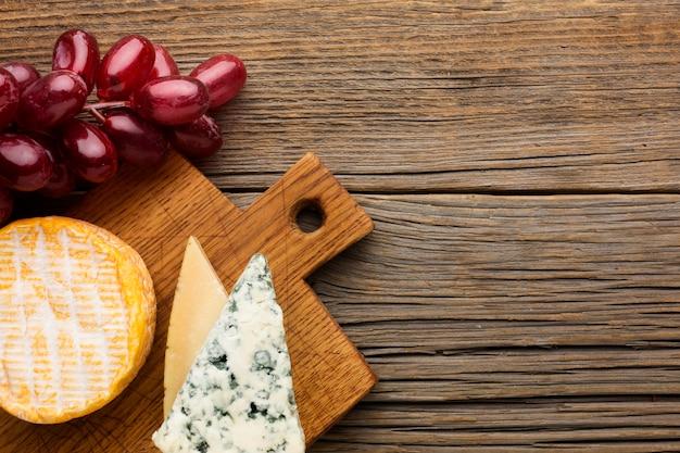 Vista superior saboroso queijo e uvas com espaço de cópia Foto gratuita