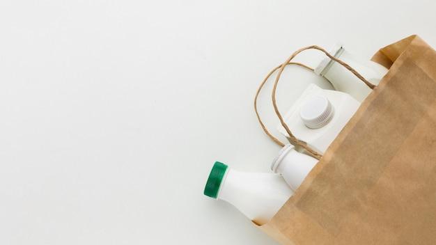Vista superior saco de papel com garrafas de leite Foto gratuita