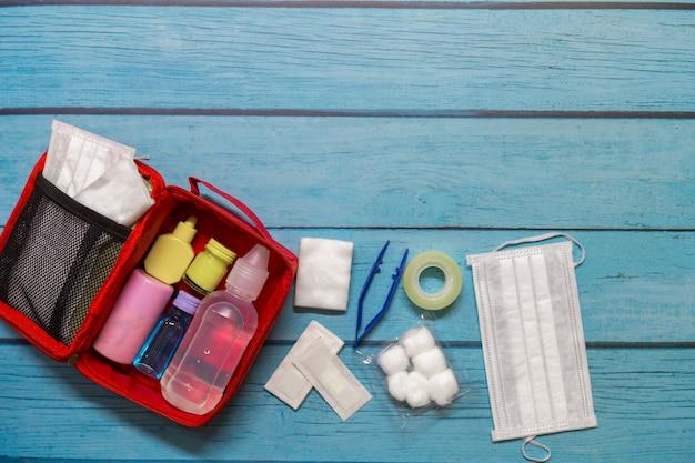 Vista superior, saco de primeiros socorros garoto com suprimentos médicos em madeira Foto Premium