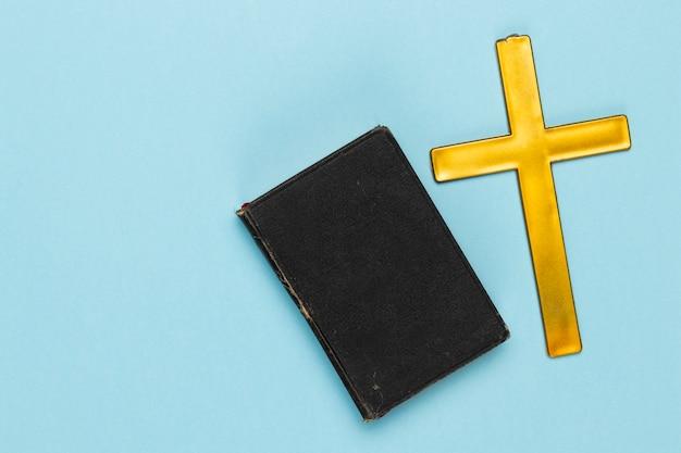 Vista superior santa cruz e livro na mesa Foto gratuita