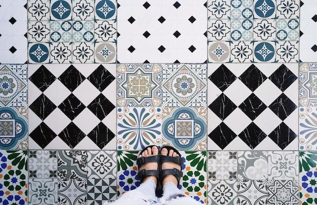 Vista superior selfie de pés em sapatos sandálias nos vários azulejos vintage Foto Premium