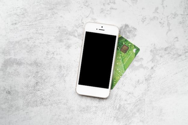 Vista superior smartphone com cartão de crédito Foto gratuita