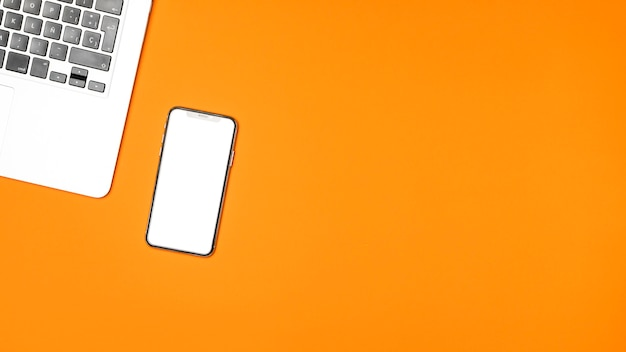Vista superior smartphone de maquete com fundo laranja Foto gratuita