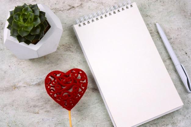 Vista superior suculenta em um pote de concreto, coração vermelho e caderno aberto com folha branca em branco Foto Premium