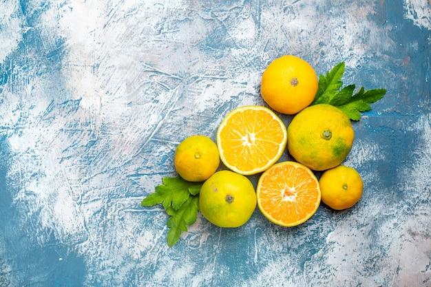 Vista superior tangerinas frescas cortadas em superfície azul e branca com espaço de cópia Foto gratuita