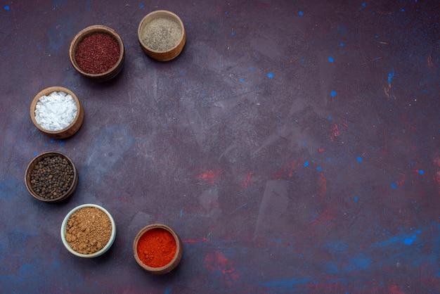Vista superior temperos dentro de potes pimenta salgada na superfície roxa escura Foto gratuita