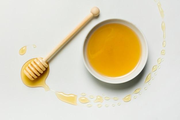 Vista superior, tigela de mel com mancha Foto gratuita