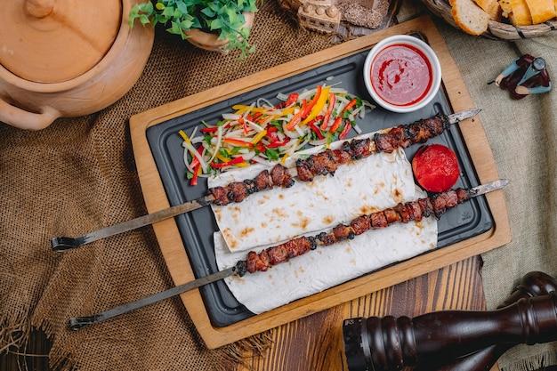 Vista superior tike kebab no espeto no pão pita com salada de legumes e ketchup Foto gratuita