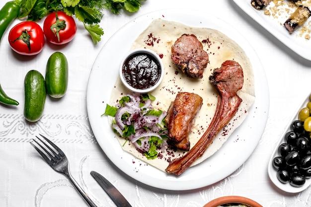 Vista superior tike kebab no pão pita com ervas e cebolas com molho e legumes Foto gratuita