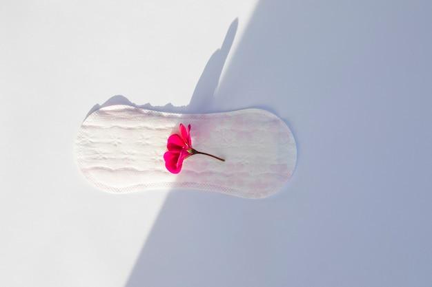 Vista superior toalha sanitária com flor Foto gratuita