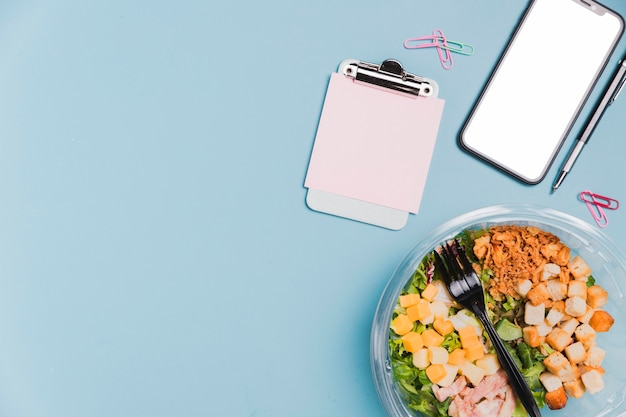 Vista superior trabalho caixa de salada com telefone em branco e cópia-espaço Foto gratuita