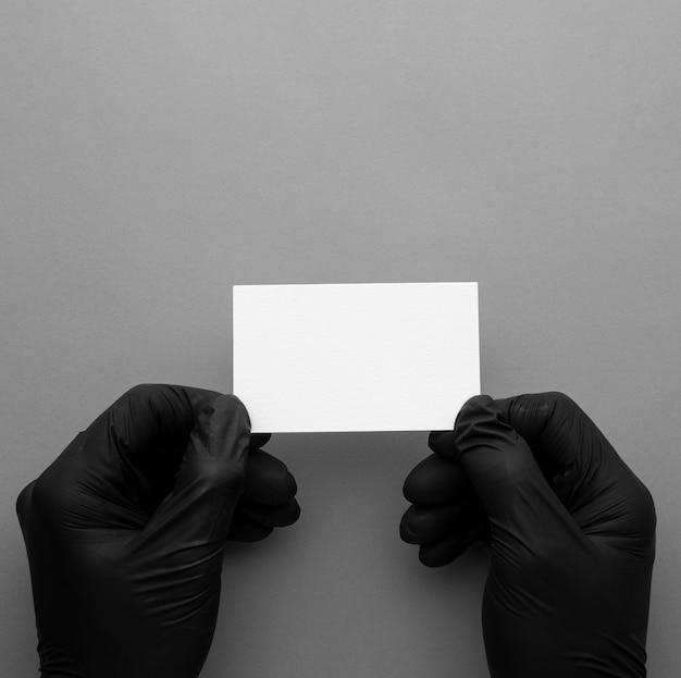 Vista superior usando luvas e segurando um cartão de visita Foto gratuita
