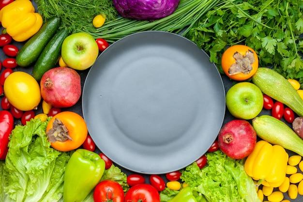 Vista superior vegetais e frutas alface tomate rabanete pepino endro tomate cereja romã caqui maçã placa cinza no centro Foto gratuita