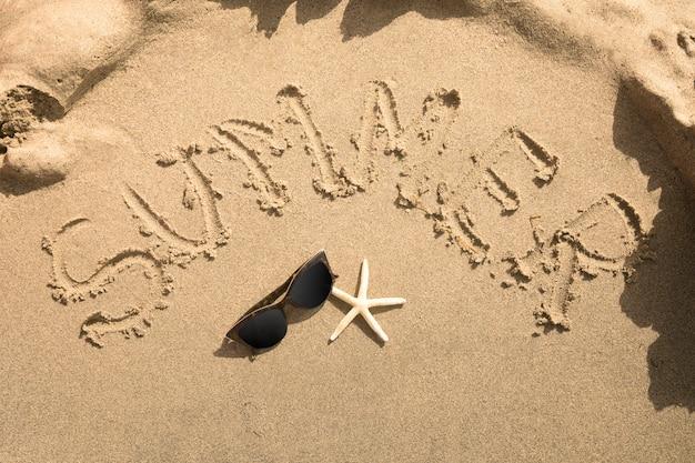 Vista superior verão escrito na areia Foto gratuita