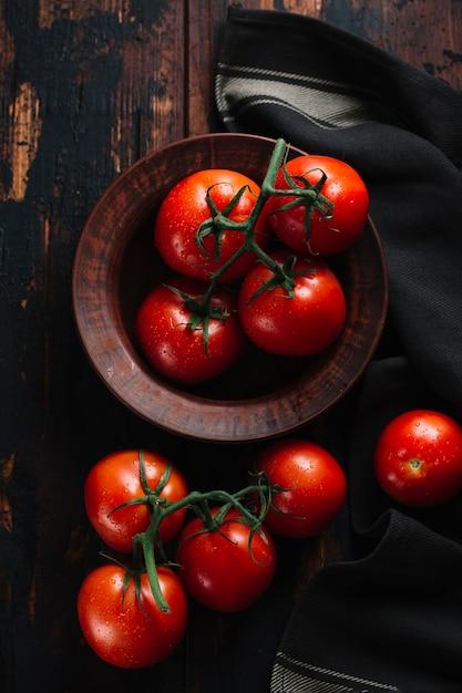 Vista superior vermelho tomate com caule em uma tigela Foto gratuita