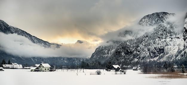 Vista típica da vila pequena dos alpes, dia de inverno nevado. Foto Premium