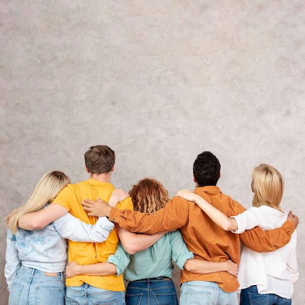 Vista traseira amigos abraçando e olhando para cima Foto gratuita