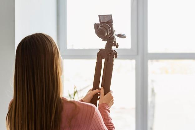 Vista traseira blogger segurando tripé com câmera Foto gratuita