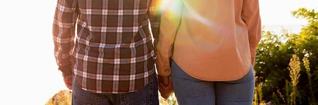 Vista traseira casal de mãos dadas Foto gratuita