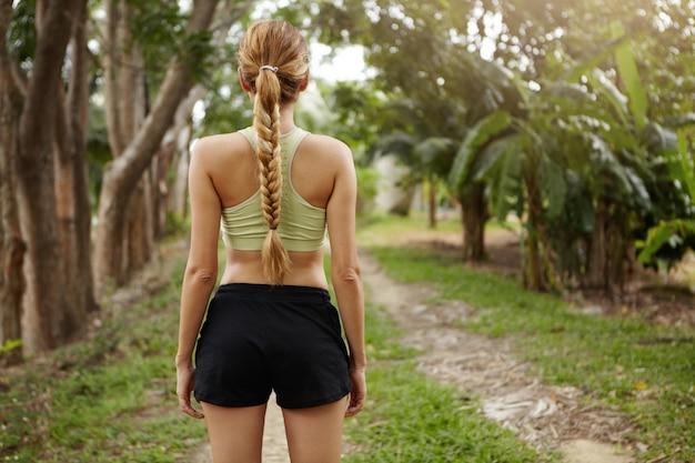 Vista traseira da atleta feminina vestindo roupa de corrida em pé na trilha em madeira pronta para correr. corredor de jovem determinado com trança longa se preparando para correr ao ar livre. Foto gratuita