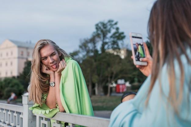Vista traseira da câmera fotografando uma jovem mulher Foto gratuita
