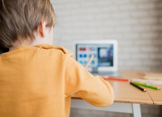 Vista traseira da criança aprendendo com o laptop em casa Foto gratuita