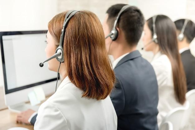 Vista traseira da equipe de agente de atendimento ao cliente de telemarketing asiático Foto Premium
