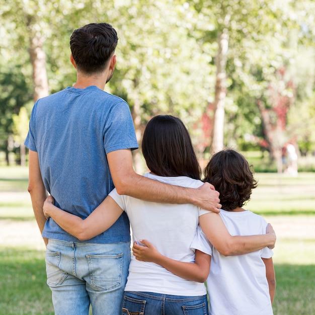 Vista traseira da família com pais e filhos abraçados Foto gratuita