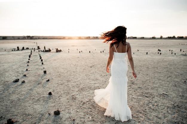 Vista traseira da garota caucasiana em vestido longo branco sem mangas à noite na área arenosa Foto gratuita