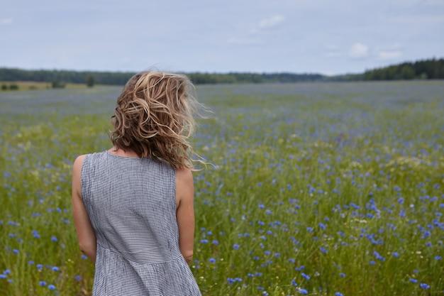 Vista traseira da garota esbelta irreconhecível, apreciando a bela paisagem, em pé no meio de um prado verde com flores azuis, seu cabelo loiro encaracolado balançando ao vento. mulher caminhando ao ar livre Foto gratuita