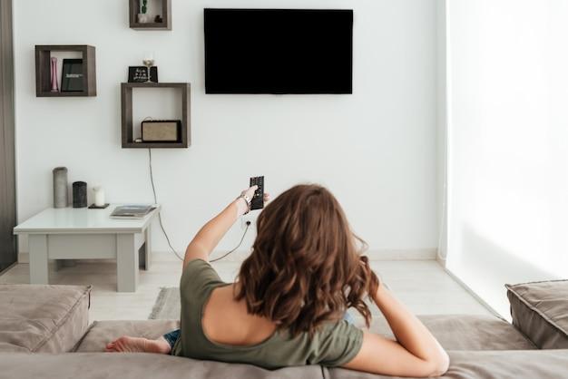Vista traseira da mulher casual, sentada no sofá e assistindo tv em casa Foto gratuita
