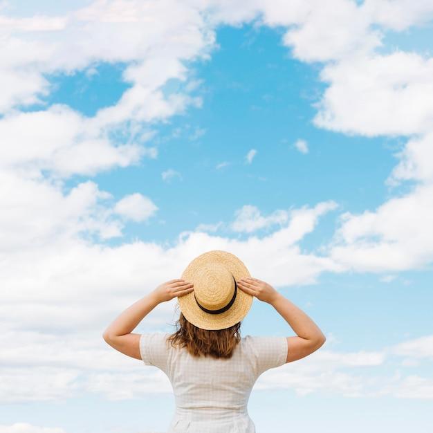Vista traseira da mulher com chapéu, admirando as nuvens no céu Foto gratuita