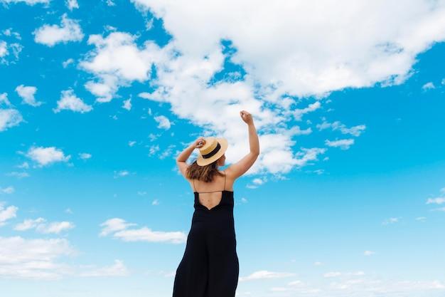 Vista traseira da mulher desfrutando da liberdade ao ar livre com céu e nuvens Foto gratuita