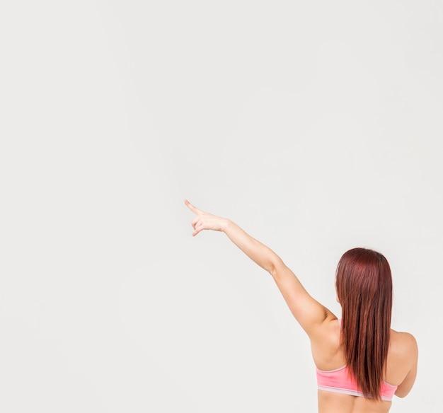 Vista traseira da mulher em roupas de ginástica, apontando para o canto esquerdo Foto gratuita