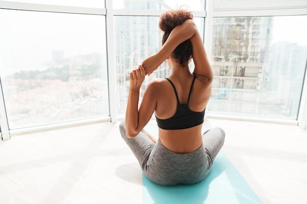 Vista traseira da mulher esticando as mãos antes do treino Foto gratuita
