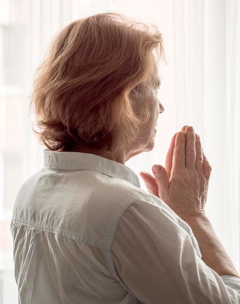 Vista traseira da mulher rezando Foto gratuita