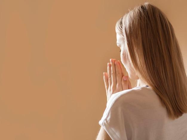Vista traseira da mulher rezando Foto Premium