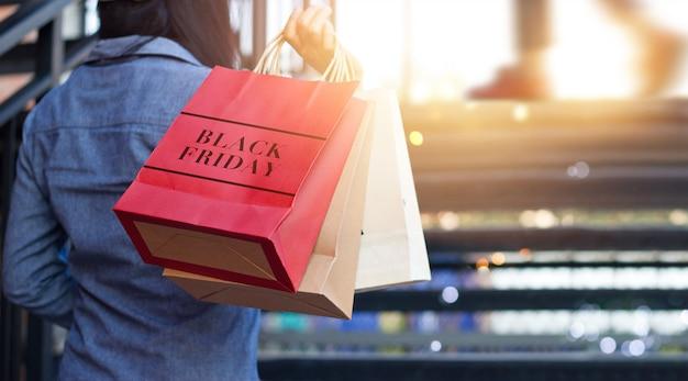 Vista traseira da mulher segurando o saco de compras de sexta-feira negra enquanto subir escadas ao ar livre no shopping Foto Premium