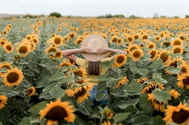 Vista traseira da mulher usando chapéu ao ar livre Foto gratuita