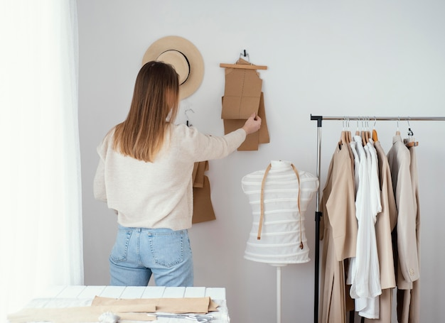 Vista traseira de alfaiate feminina no estúdio com roupas Foto gratuita