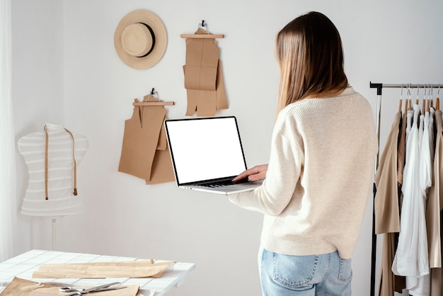 Vista traseira de alfaiate feminina no estúdio usando laptop Foto gratuita