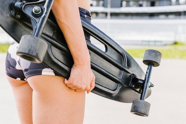 Vista traseira, de, atleta, segurando, longboard Foto gratuita